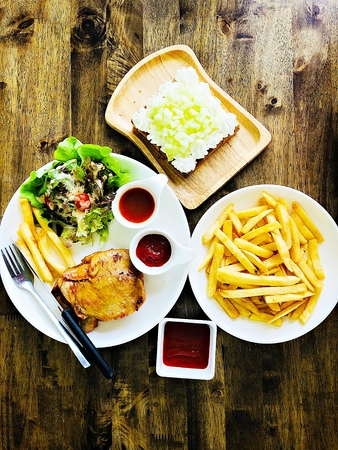 Food concept : Top view of grilled chicken steak, french fries or potato fries with ketchup and melon fruit toast on wooden table