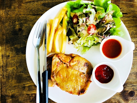Food concept : Top view of grilled chicken steak with salad and french fries on wooden table Archivio Fotografico