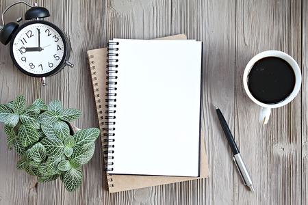Still life, business, planning or working concept : Open notebook with blank pages, coffee cup and clock on wooden desk table, top view or flat lay with copy space ready for adding or mock up Archivio Fotografico