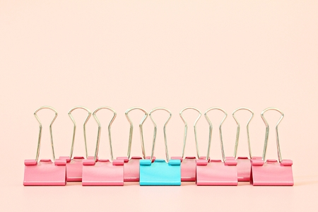 Business, office supplies, leadership, unique, individuality or think different concept : Blue binder clip standing out of pink binder clips on pink background with copy space Archivio Fotografico