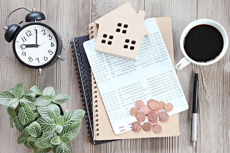 Business, finance, savings, money management, property loan or mortgage concept :  Top view or flat lay of wood house model, savings account book or financial statement and coins on office desk table