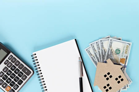 Business, finance, saving money, property ladder or mortgage loan concept : House model, American Dollar cash money, notebook and calculator on office desk table Archivio Fotografico