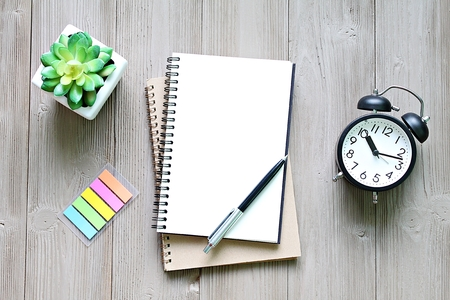 Still life, business, goals, planning, meeting or working concept : Open notebook with blank pages, and clock on wooden desk table, top view or flat lay with copy space ready for adding or mock up