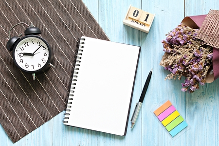 Business, still life, working, holiday or new year planning concept : Desk table with open notebook paper, cube calendar and clock, Top view or flat lay with copy space ready for adding or mock up Archivio Fotografico