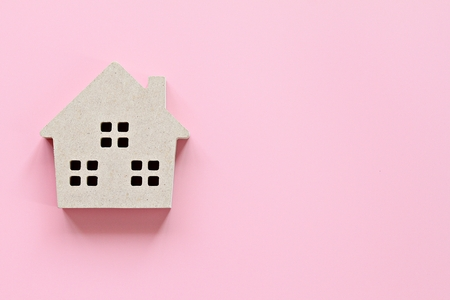 Business, finance, savings, money management, property loan or mortgage concept :  Top view or flat lay of wood house model on pink background with copy space ready for adding or mock up