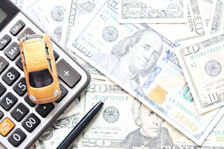 Business, finance, saving money, banking or car loan concept : Top view or flat lay of miniature car model, calculator and pen on American Dollars cash money