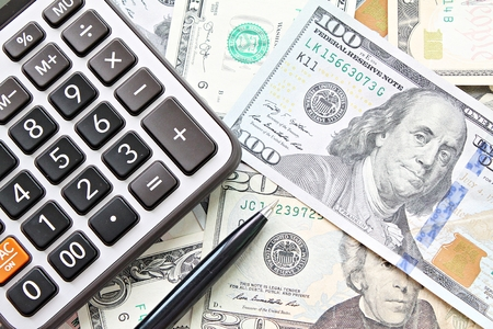 Business, finance, investment, accounting, taxes or money exchange concept : top view or flat lay of calculator and pen on American Dollars cash money Archivio Fotografico