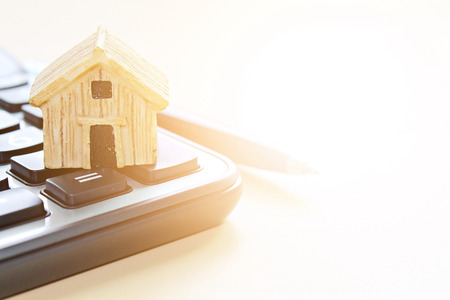 Business, finance, savings, money management, property loan or mortgage concept :  Wood house model on calculator