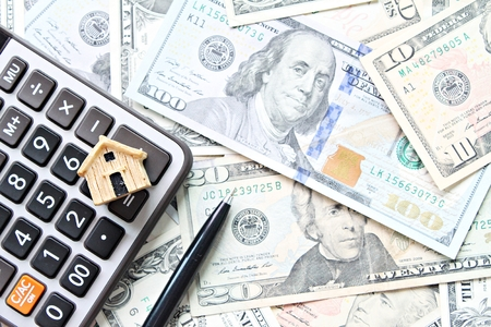 Business, finance, savings, money management, property loan or mortgage concept : Top view or flat lay of wood house model, calculator and pen on American Dollars cash money