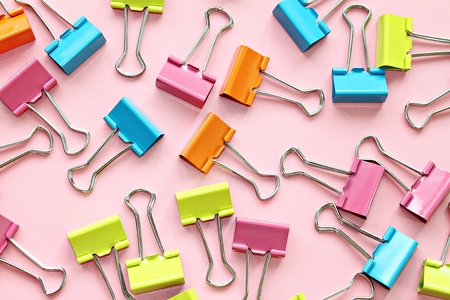 Business, office supplies, teamwork, corporation, collaboration or unity concept : Top view or flat lay of multi colored binder clips on pink background Archivio Fotografico