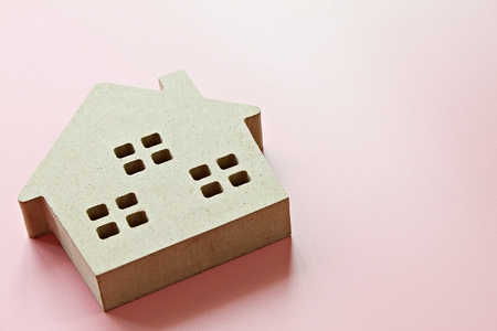 Business, finance, savings, money management, property loan or mortgage concept :  Wood house model on pink background with copy space ready for adding or mock up