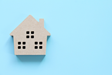 Business, finance, savings, money management, property loan or mortgage concept :  Top view or flat lay of wood house model on blue background with copy space ready for adding or mock up