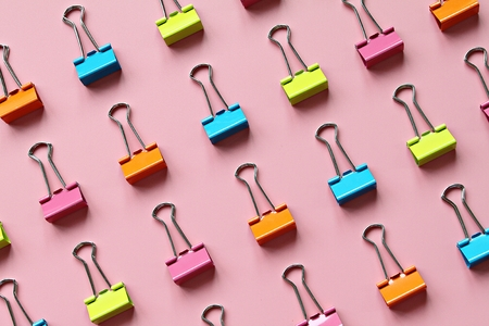 Business, office supplies, teamwork, corporation, collaboration or unity concept : Lines of multi colored binder clips on pink background
