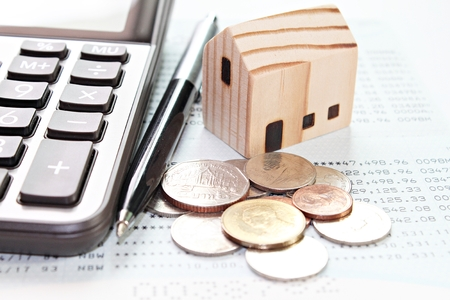 Business, finance, savings, money management, property loan or mortgage concept : Wood house model, calculator, pen and coins  on financial statements or savings account passbook
