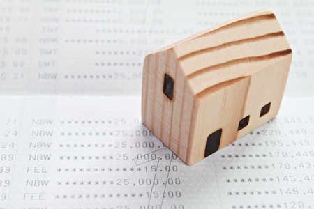 Business, finance, savings, money management, property loan or mortgage concept : Wood house model on financial statements or savings account passbook with copy space ready for adding or mock up