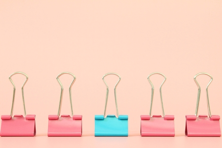 Business, office supplies, leadership, unique, individuality or think different concept : Blue binder clip standing out of pink binder clips on orange background with copy space for adding or mock up
