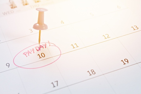 Business, finance, savings money, wages, payroll or accounting concept : Blue thumbtack on calendar with pink marker circle in word payday for remind Zdjęcie Seryjne