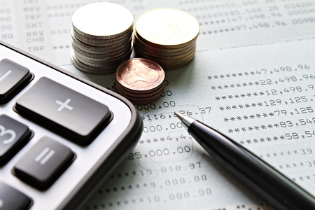 Business, finance, saving money, taxes, accounting or investment concept : Coin stacks, calculator, pen and savings account passbook or financial statement on office desk table