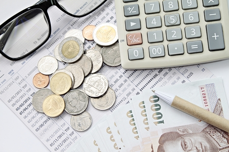 Business, finance planning, saving money, taxes or accounting concept : Top view or flat lay of coins, cash money, calculator and pen on savings account book or financial statements