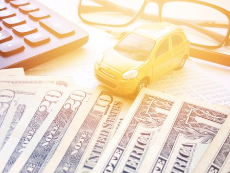Business, finance, saving money or car loan concept : Miniature car model, American Dollars cash money, calculator and saving account book or financial statement on office desk table