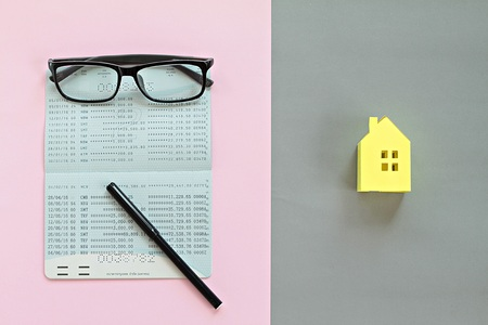 Business, finance, saving money, property ladder or mortgage concept : Top view or flat lay of savings account passbook and yellow paper house model on background Archivio Fotografico