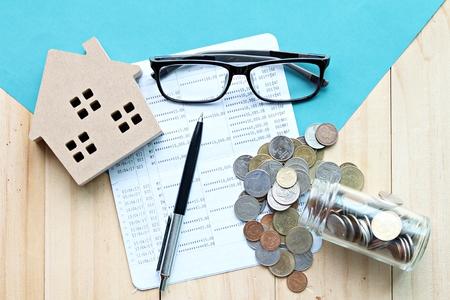 Geschäfts-, Finanz-, Spar-, Geldmanagement-, Immobiliendarlehens- oder Hypothekenkonzept: Draufsicht oder flache Lage des Holzhausmodells, Sparbuch oder Jahresabschluss und Münzen auf dem Schreibtischtisch Standard-Bild