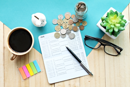 Business, finance, saving money, investment or accounting concept :  Top view or flat lay of piggy bank, saving account book or financial statement and coins on office desk table