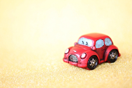 Business, finance, saving money, banking or car loan concept : Miniature car model on gold glitter lighting background with copy space ready for adding or mock up