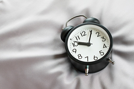 Still life, business deadline, meeting, time management, savings time, relax, weekend or holiday concept concept : Top view of black retro alarm clock on bed in morning, ready for adding or mock up
