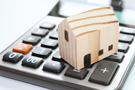 Business, finance, savings, money management, property loan or mortgage concept :  Wood house model on calculator Archivio Fotografico - 126599880