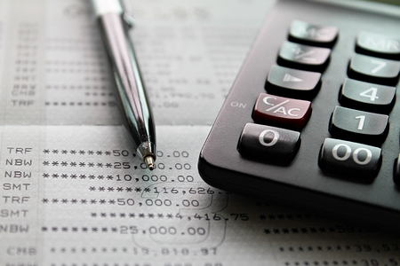 Business, finance, investment, accounting or taxes concept : Top view or flat lay of calculator and pen on savings account passbook or financial statement