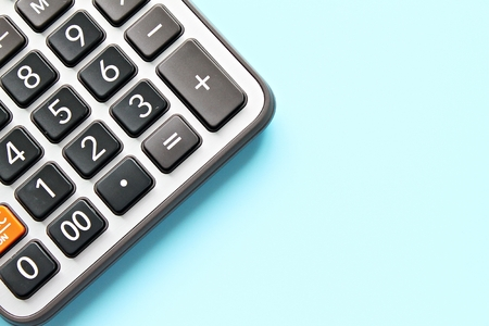 Business, finance, savings money, investment, taxes or accounting concept : Top view or flat lay of calculator on blue background with copy space ready for adding or mock up