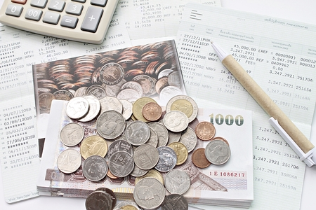 Business, finance, saving money, taxes or accounting concept : Top view or flat lay of coins, cash money, calculator and pen on savings account book or financial statements