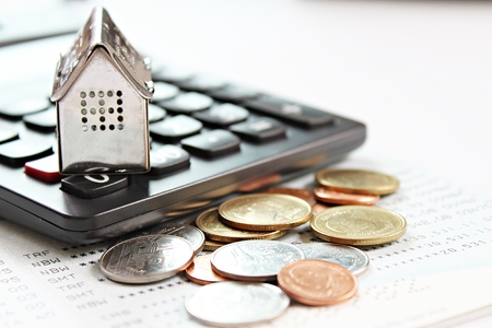 Affaires, finance, économies d'argent, échelle de propriété ou concept de prêt hypothécaire : modèle de maison, calculatrice et pièces sur livret de compte d'épargne ou états financiers