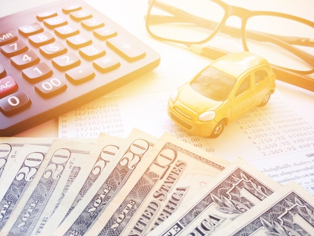 Business, finance, saving money or car loan concept : Top view or flat lay of miniature car model, American Dollars cash money, calculator and saving account book or financial statement on office desk Zdjęcie Seryjne