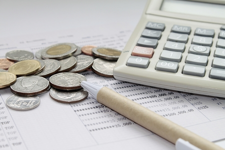 Business, finance, investment, taxes, accounting or money exchange concept : Calculator, pen and coins on savings account passbook or financial statement