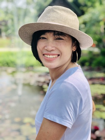 People, beauty, fashion, vacation or happy life concept : Outdoors close up portrait of girl smiling or Asian woman smiling in the park and looking at camera
