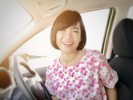 People, happy life, business, finance or car loan concept : Selfies of girl smiling or Asian woman smiling in the car and looking at camera