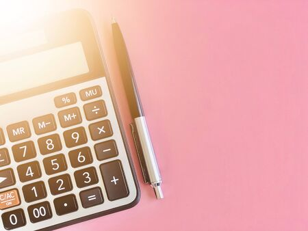 Business, finance, savings money, investment, taxes, money planning or accounting concept : Top view or flat lay of calculator and pen on pink background with copy space ready for adding or mock up