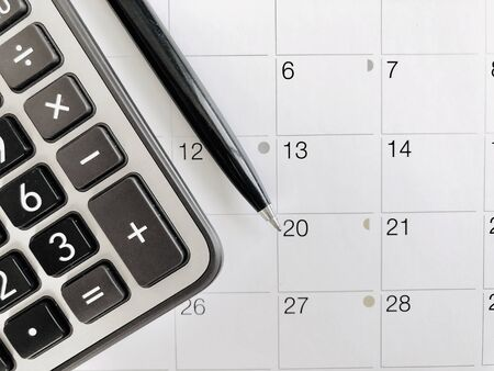 Business,finance, taxes, accounting, wages, payroll or money planning concepts : Top view or flat lay of calculator and pen on calendar