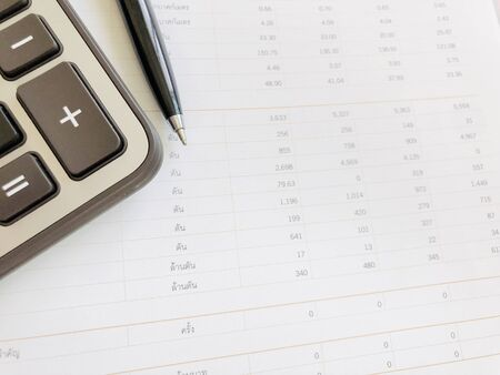 Business,finance, taxes, accounting, investment or money planning concepts : Calculator and pen on financial statements