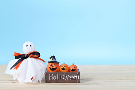 Halloween holiday background concept : Halloween decoration with ghost on table and blue background with copy space, ready for adding or mock up