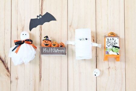 Halloween holiday background concept : Top view or flat lay of Halloween decoration with ghosts and bat on wooden background with copy space, ready for adding or mock up