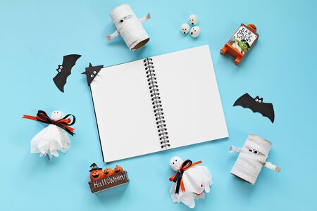Halloween holiday background concept : Top view or flat lay of notebook paper with Halloween decoration, ghosts and bat on blue background with copy space, ready for adding or mock up