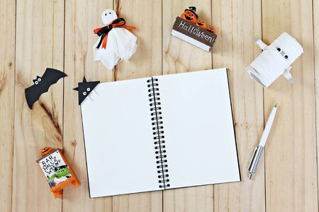 Halloween holiday background concept : Top view or flat lay of Notebook paper with Halloween decoration, ghosts and bat on wooden background with copy space, ready for adding or mock up