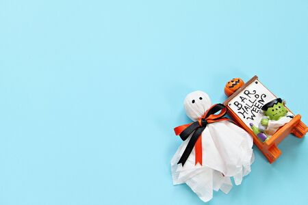 Halloween holiday background concept : Top view or flat lay of Halloween decoration with ghost on blue background with copy space, ready for adding or mock up