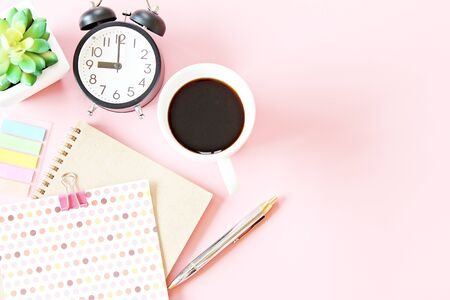 Still life, business, office supplies, working day, meeting or education concept : Top view of notebook, clock, pen and coffee cup on pink background with copy space ready for adding or mock up Zdjęcie Seryjne