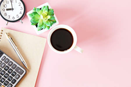 Top view or flat lay of notebook paper with pen, calculator, clock and coffee cup