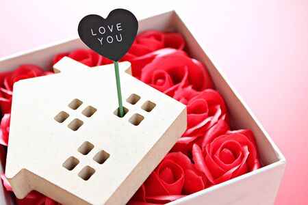 Business, finance, property ladder, mortgage loan, love, gifts or Valentine's day concept : Wood house model with love you tag and red roses on red background with copy space for adding or mock up