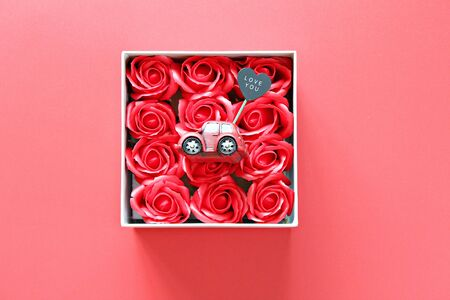 Business, finance, car loan, love, gifts or Valentine's day concept : Miniature car model with love you on heart tag and red roses box on red background